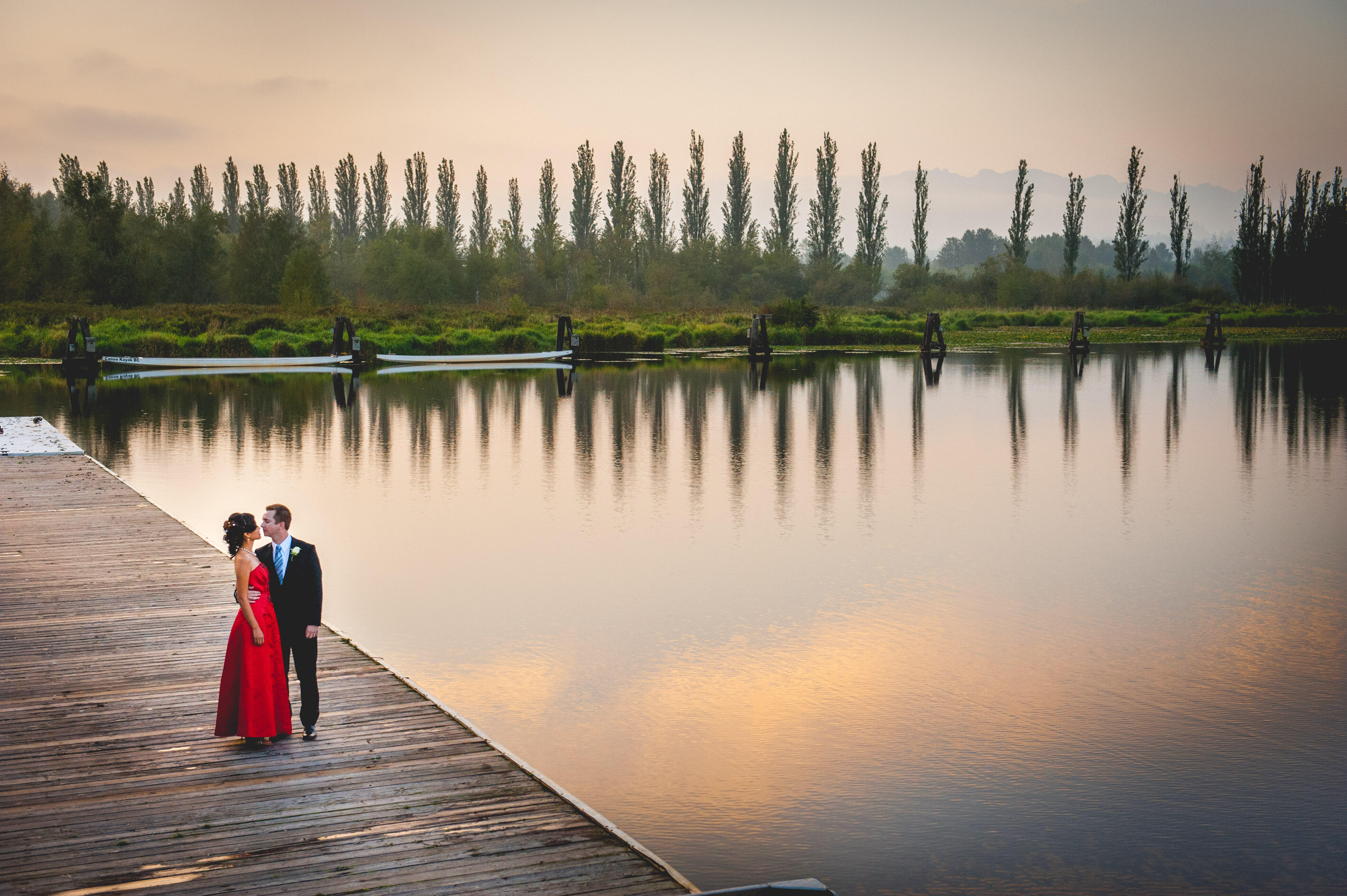 A couple is about to kiss beside the lake