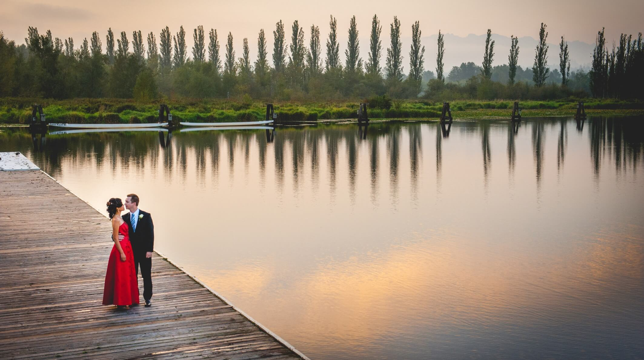 Couple standing on the dock by a lake at dusk.