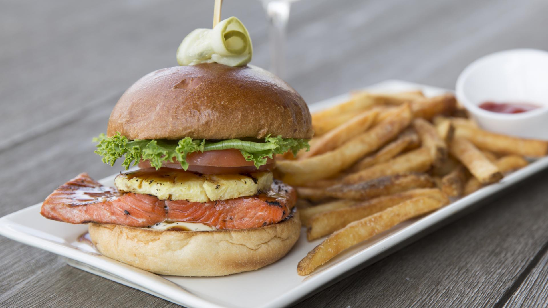 Grilled Salmon Burger - grilled pineapple, lettuce, tomato, teriyaki sauce and lemon aoli on a fresh brioche bun