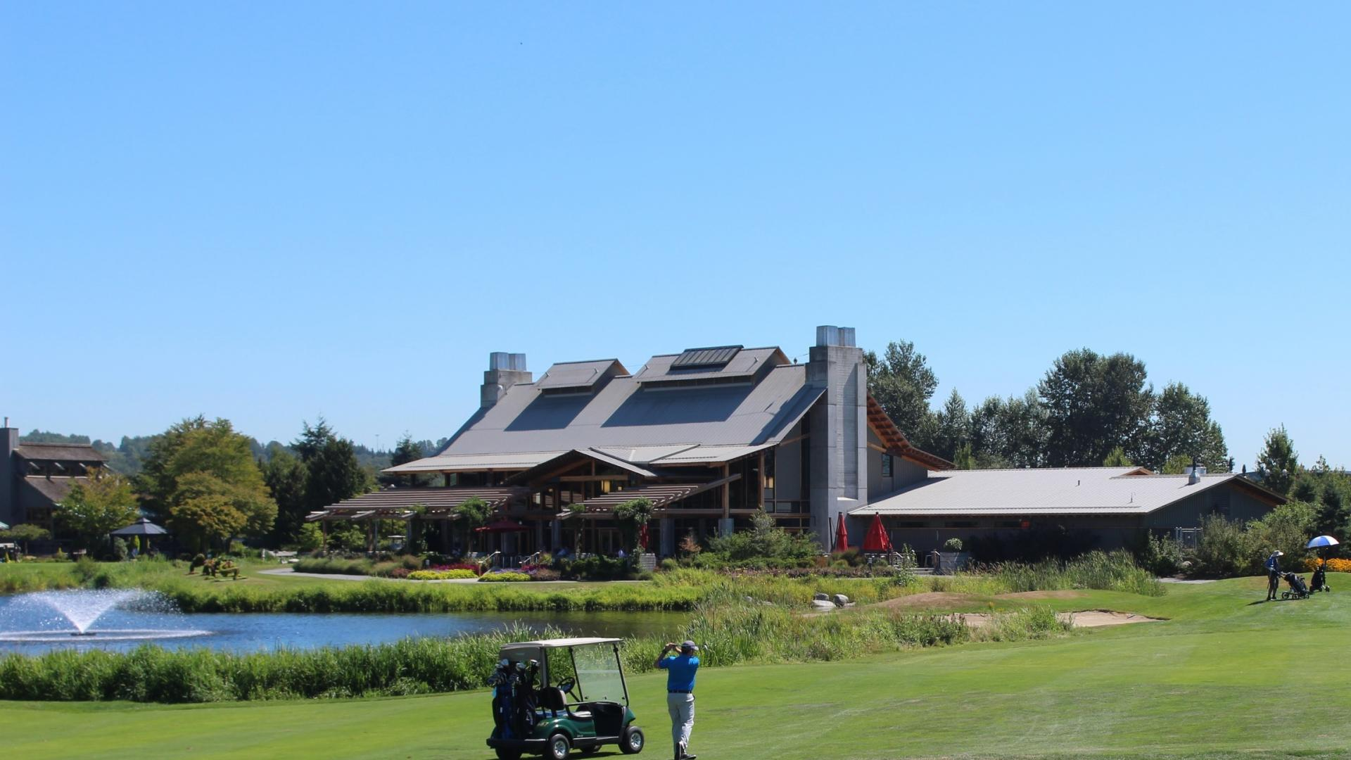 Riverway Clubhouse serves as the backdrop for a golfer taking a swing